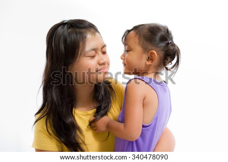 Asian Little Girl Playing Fun Games Together with Teen Nanny - stock photo