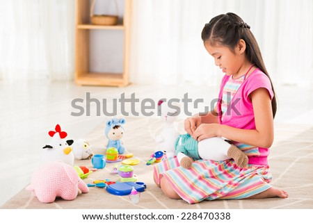 Asian little girl playing with knitted toys  - stock photo