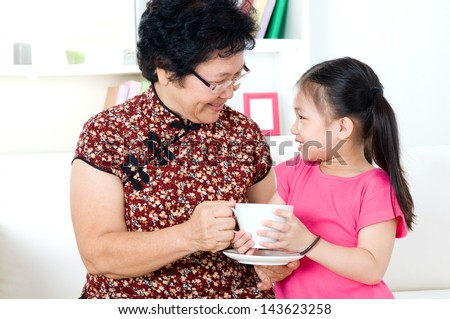 Asian little girl presenting tea to grandmother - stock photo