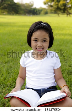 Asian little girl reading book