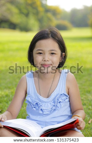 Asian little girl reading book in the park