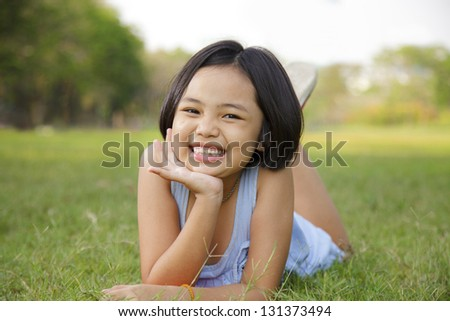Asian little girl relax and smiling happily in the park - stock photo