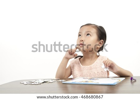 Asian little  girl thinking of that solve the puzzle with finger.