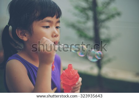 Asian  little  girl  with water bubble  in vintage  color  filter tone