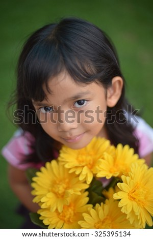 Asian little girl with yellow flowers in garden
