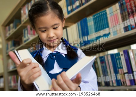 Asian little student in library - stock photo