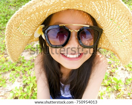 Asian long black hair girl is smiling and wearing white vest, blue jeans trousers, black sunglasses, straw hat and white flower behind the right ear.