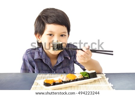 Asian lovely boy is eating sushi isolated over white background