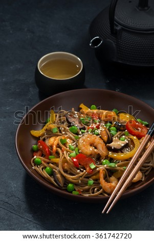 Asian lunch. Buckwheat noodles with seafood, vertical, closeup