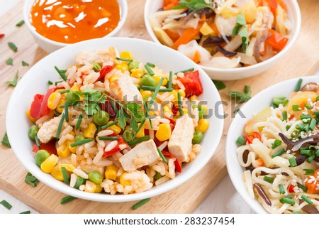Asian lunch - fried rice with tofu, noodles with vegetables and herbs, top view, horizontal - stock photo