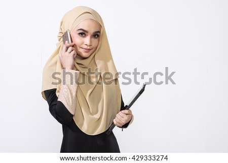 asian malay woman using a mobile phone while holding a tablet for bussines matter - stock photo