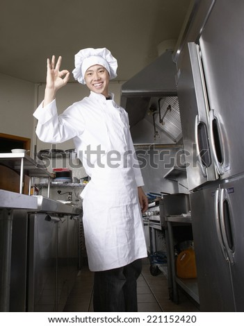 Asian male chef making OK hand gesture