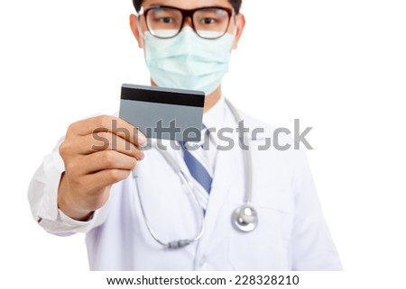 Asian male doctor wear mask with credit card  isolated on white background - stock photo
