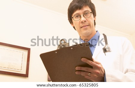 Asian male doctor with chart - stock photo