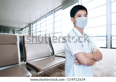 Asian male doctor with face mask portrait standing inside hospital building - stock photo