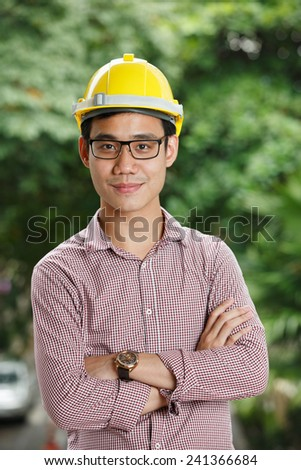 Asian male engineer with a yellow hard hat - stock photo