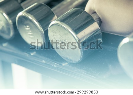 Asian male  hand grab dumbell  focused on 5 kg one with soft light - stock photo