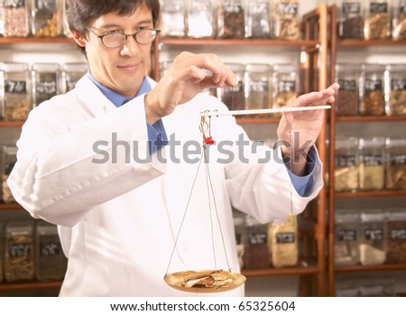 Asian male herbalist doctor weighing Chinese medicinal herbs - stock photo