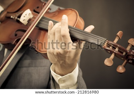Asian male Musician plays Violin on Dark Background / sepia processed - stock photo