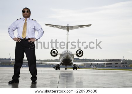 Asian male pilot with airplane in background - stock photo