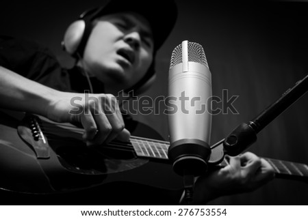asian male singer,guitarist,musician play guitar & singing on condenser microphone in music recording studio / black and white processed - stock photo