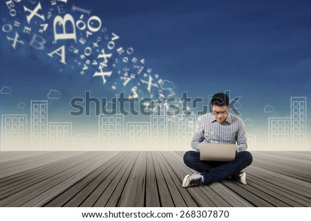 Asian male student send email message using laptop sitting outdoor - stock photo