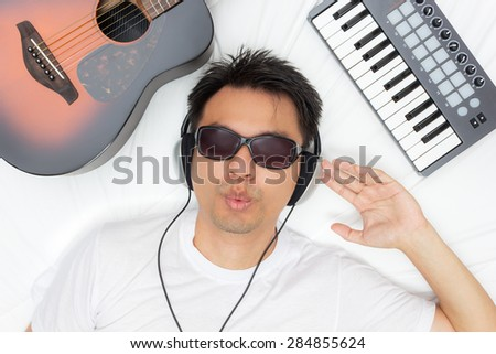 asian male whistler lying on white bed while listening music through headphone & guitar, piano - stock photo