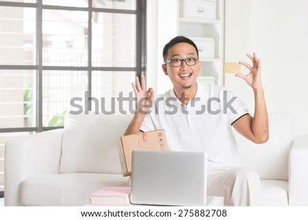 asian male with credit card doing online shopping - stock photo