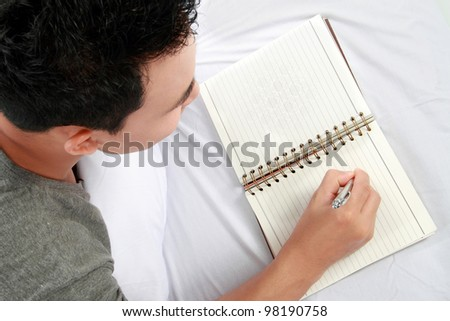 Asian male writing on his diary while lying on the bed