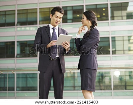 asian man and woman discussing business.