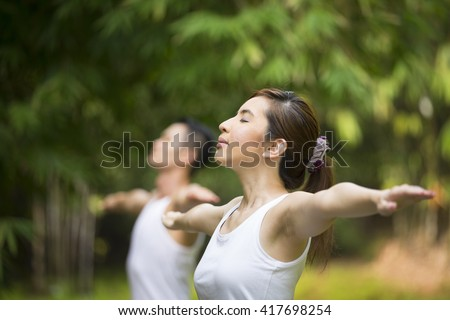 Asian Man and woman doing Tai Chi in a garden. Healthy lifestyle and relaxation concept. - stock photo