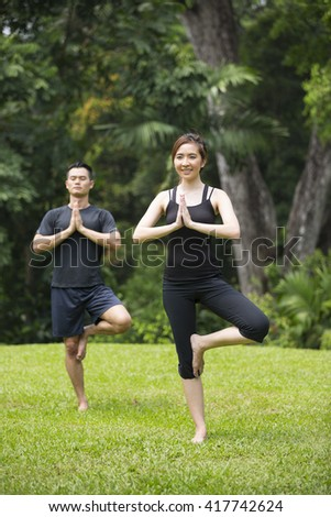 Asian Man and woman doing yoga in a garden. Healthy lifestyle and relaxation concept. - stock photo
