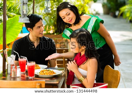 Asian man and woman in restaurant are being served food by the waitress - stock photo