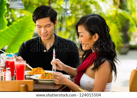 Asian man and woman in restaurant eating their food with chopsticks - stock photo