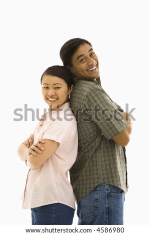 Asian man and woman standing back to back and smiling.