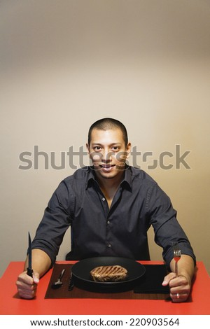 Asian man at dinner table with steak - stock photo