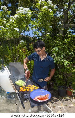asian man barbecuing in his garden - stock photo