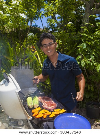 asian man barbecuing in his garden