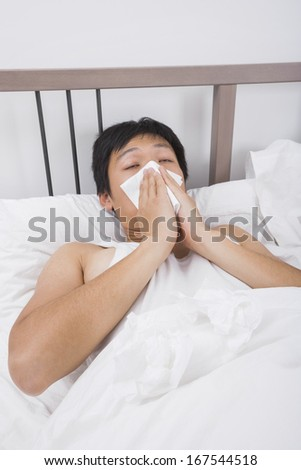 Asian man blowing nose in bed