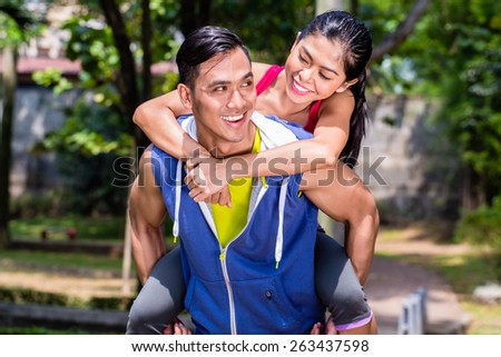 Asian man carrying his girlfriend piggyback for sport in a break during his sport training - stock photo