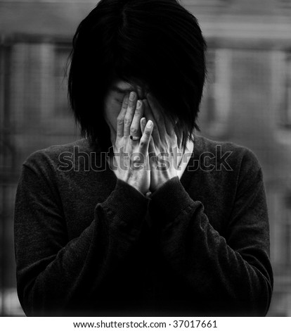 Asian man covered eyes with hands - stock photo