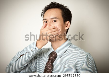 Asian man covering his mouth by the hand - stock photo