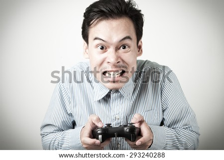 Asian man crazy gamer with joystick game controller. - stock photo