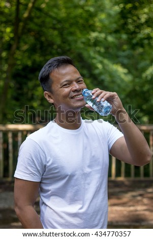 asian man drinking water from a bottle, outdoor