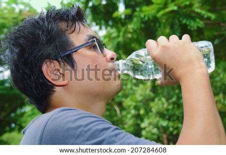 asian man drinking water in the park