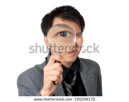 Asian man eye look thru a magnifier ,isolated
