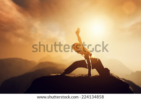 Asian man, fighter practices martial arts in high mountains at sunset. Kung fu and karate pose. Also concepts of discipline, concentration, meditaion etc. Unique - stock photo