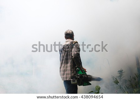 Asian man fogging mosquitoes - stock photo