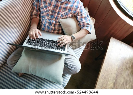 Asian man hand using laptop connect with internet working on sofa.