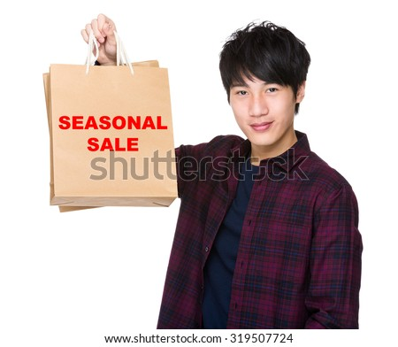 Asian Man hold with shopping bag and showing pharse of seasonal sale